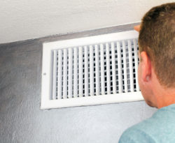 Man removing vent cover for residential air duct cleaning